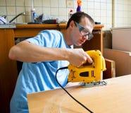 Man att förbereda sig att klippa trä med en jigsaw Royaltyfri Bild