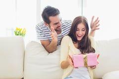 Man att förvåna hans flickvän med en gåva på soffan Arkivfoton