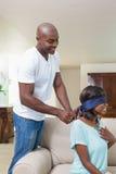 Man att förvåna hans flickvän med en halsband på soffan Royaltyfri Fotografi