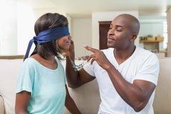 Man att förvåna hans flickvän med en halsband på soffan Royaltyfri Foto