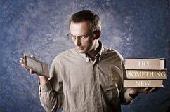 Man att fokuseras på den ljusa och behändiga ebookavläsaren, hållande skurkrollböcker i annan hand, försök något nytt skriftligt  Arkivbild