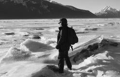 Man att fotvandra nära en djupfryst flod med isstora bitar Royaltyfri Bild