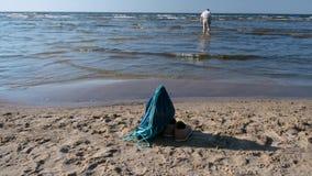 Man att gå bort på grunt vatten, ryggsäcken och kängor som lämnas på stranden arkivfilmer