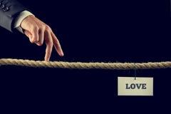 Man att gå hans fingrar längs en längd av repet in mot förälskelse Arkivfoto