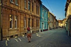 Man att gå i den gamla delen av staden av Brasov Rumänien, den Postavaru gatan arkivbild