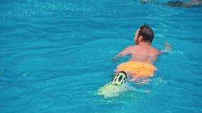 Man att gå i simbassängen på solig dag arkivfilmer