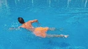 Man att gå i simbassängen på solig dag stock video