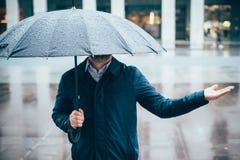 Man att gå i staden med paraplyet på regnig dag arkivfoto