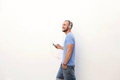 Man att gå med mobiltelefonen som lyssnar till musik på hörlurar Royaltyfria Bilder