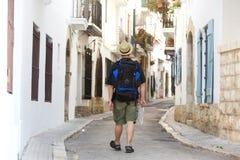 Man att gå med ryggsäcken och kartlägga borttappat i stad Royaltyfri Bild