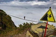 Man att gå på upphängningbron och att se molniga berg under arkivbilder