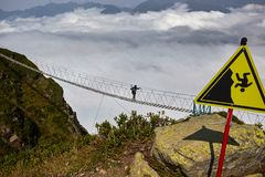 Man att gå på upphängningbron och att se molniga berg under royaltyfri fotografi
