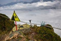 Man att gå på upphängningbron och att se molniga berg under royaltyfria foton