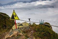 Man att gå på upphängningbron och att se molniga berg under royaltyfri foto