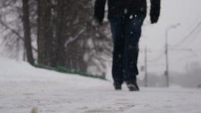 Man att gå på vägen på en snöig dagrearview stock video