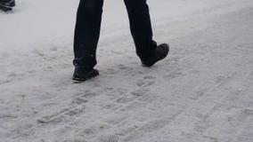 Man att gå på vägen på en snöig dagvideo lager videofilmer