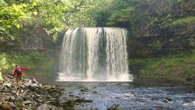 Man att gå vid den Sgwd år Eiravattenfallet, Brecon fyrnationalpark lager videofilmer