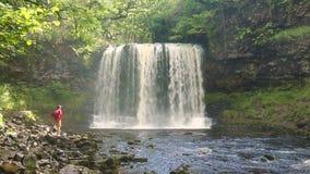 Man att gå vid den Sgwd år Eiravattenfallet, Brecon fyrnationalpark arkivfilmer