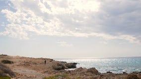 Man att gå vid den steniga stranden på en härlig solig dag cyprus stock video