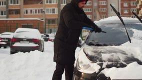 Man att göra klar hans bil med borsten från insnöat gården stock video