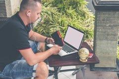 Man att göra online-shopping med den kreditkort-, bärbar dator- och för lyxsnakeskinpytonormen plånboken Manonline-shoppingbegrep royaltyfria bilder
