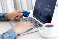 Man att göra online-shopping med kreditkorten på bärbara datorn Arkivfoto