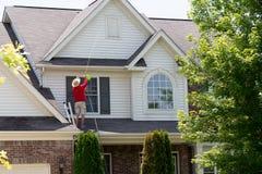 Man att göra ren övregolvyttersidan av hans hem fotografering för bildbyråer