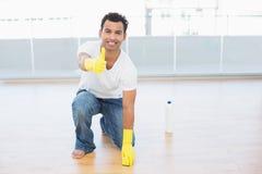 Man att göra ren golvet, medan göra en gest upp tummar på huset arkivfoto