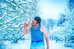 Man att göra ren hans tänder förbi trädfilialen på vintern Arkivfoto