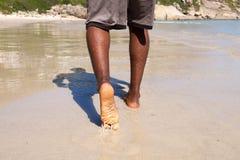 Man att gå med kal fot på stranden Arkivfoto