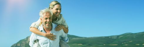 Man att ge hans skratta fru en ridtur på axlarna på stranden arkivbild