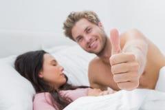 Man att ge upp tummen bredvid hans sova fru Royaltyfria Bilder
