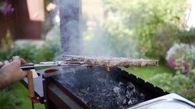 Man att grilla grisköttkött på fyrpannan som bläddrar stycken arkivfilmer