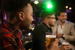 Man att ha öl med hans vänner i en bar arkivfoton