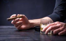 Man att ha en drink och att röka på en stång arkivfoton