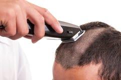 Man att ha en frisyr med hårnagelsax över en vit backgroun Arkivbild