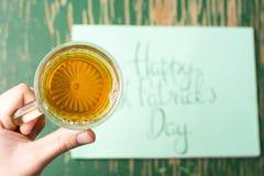 Man att ha ett öl med det lyckliga St Patrick dagkortet Arkivfoton