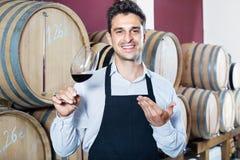Man att ha exponeringsglas med vinprövkopian i alkoholavsnitt Arkivfoton