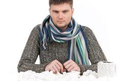 Man att ha förkylning med silkespappret på tabellen och asken av silkespapper Royaltyfri Bild