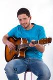 Man att ha gyckel från att spela på den akustiska gitarren Fotografering för Bildbyråer