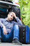 Man att ha problem med emballagebagage in i en bil Arkivbilder