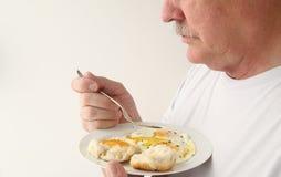 Man att ha stekt ägg och kexet med kopieringsutrymme Arkivbild