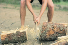 Man att hugga av vedträ med en yxa på en sandig strand i rörelse royaltyfri bild