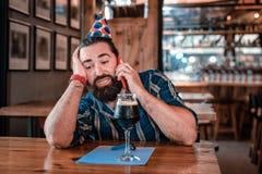 Man att kalla hans vänner som väntar på dem i bar på hans födelsedag royaltyfri fotografi