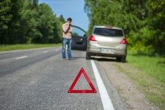 Man att kalla till en bilhjälp efter sammanbrott Royaltyfria Bilder