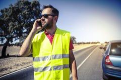 Man att kalla till försäkringsbolag efter en bilsammanbrott Royaltyfria Bilder