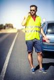 Man att kalla till försäkringsbolag efter en bilsammanbrott Fotografering för Bildbyråer