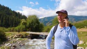 Man att kalla till mobiltelefonen och bron över den steniga floden som flödar i berg stock video