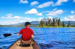 Man att kanota på en sjö i British Columbia, Kanada Royaltyfria Bilder