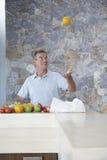 Man att kasta apelsinen in i luft på diskbänken royaltyfria foton
